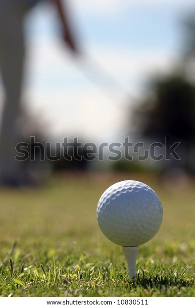 A golf ball sitting on the tee while a golfer ahead tees off.