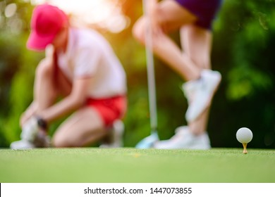 golf ball stansing on wooden TEE ready to serving hit by the golfer on the T-OFF, woman golf players are in relax feeling before goiong to hot to ball to fairway in sunny day