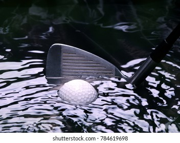Golf ball stuck in a water hazzard with iron club