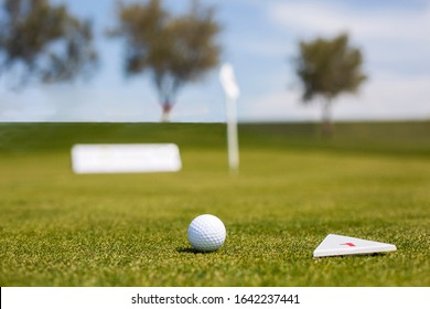 Golf ball and swing on the grass, towel and colorful golf balls, golf flag