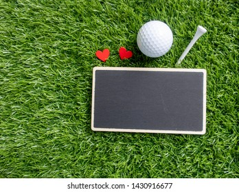 Golf ball with tee and chalkboard on green grass