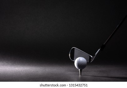 Golf ball, tee and iron on black background