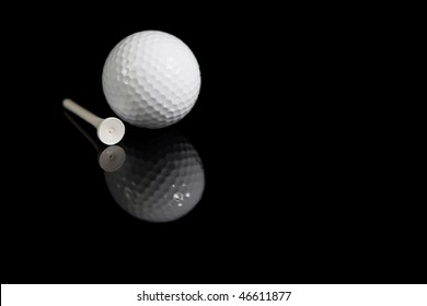 Golf Ball and Tee on black background with reflection