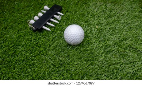 Golf ball and tee are on green grass