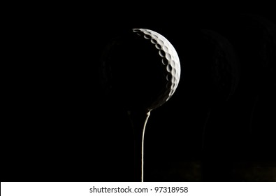 Golf ball and tee in strong sidelighting making a question mark against a black background.
