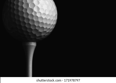 Golf Ball Teed Up Close Up against a Black Background; low key silhouette