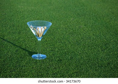 golf ball and tees in martini glass