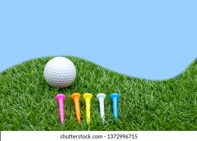 Golf ball and tees are on green grass.