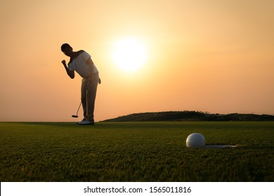 Golf ball that is about to hole together with the golfer hold a putter and lift up fist in background amid the golden sky of the evening sun. - Shutterstock ID 1565011816