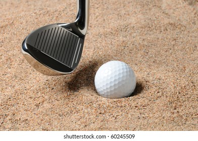 Golf Ball in Trap with Sand Wedge about to strike the golfball. Close up in horizontal composition with copy space.