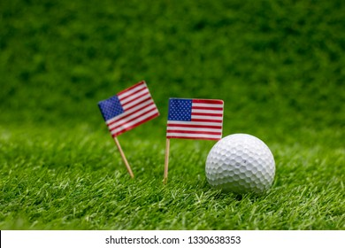 Golf ball with U.S.A. flag are on green grass