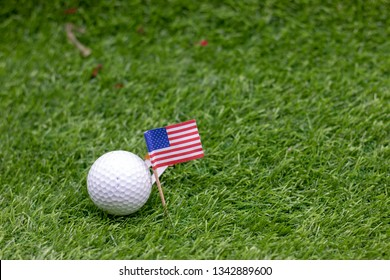 Golf Ball with U.S.A. flag are on green grass for 4th July.