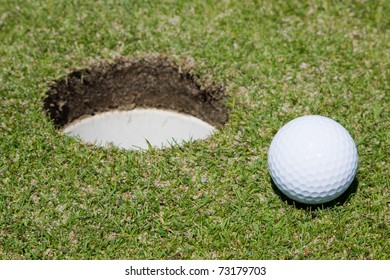 Golf ball very close to a hole on a putting green.