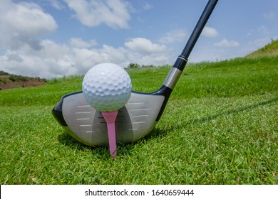 Golf ball white dimples detail on pink plastic tee peg with metal driver club closeup on green grass with blue sky.