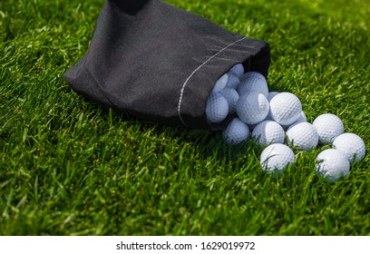 Golf balls in the bag on the grass, daylight, close up shot, white golf balls