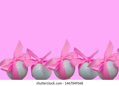 Golf balls with pink ribbon are isolated on pink background.