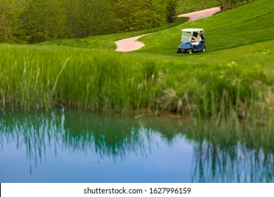 Golf buggy on the bank of the lake, no people, sunny day and green grass.