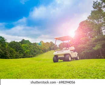 golf car or cart on beautiful fairway on layout of golf course. Player see beauty of sky and cloud with green grass and large trees litter. Course with beautiful light in sunset and sunshine for play