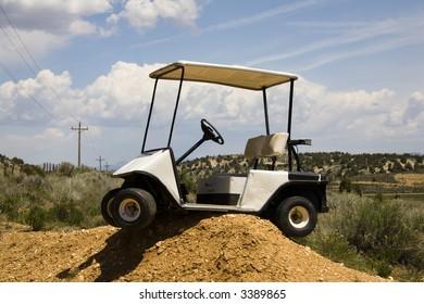 Golf cart high centered on a dirt mound