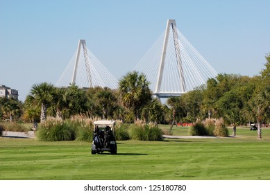 Golf cart on course with bridge in background