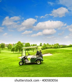 Golf cart on a golf course. Green field and cloudy blue sky. Spring landscape with fresh grass and trees. Vibrant colors