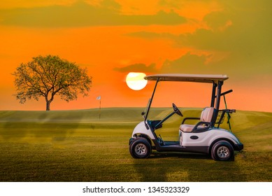 A Golf cart parking on green grass at golf course with big tree and sun set sky background