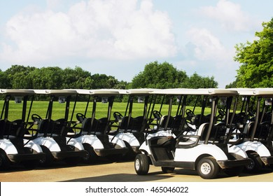 Golf carts are waiting for the players. Sunny summer day and cloudy sky over a golf course. Horizontal shot.
