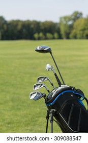 Golf club against the background of green field. Golf organizer cart bag with golf clubs. It is nice idea to spend your vacation during summer time.