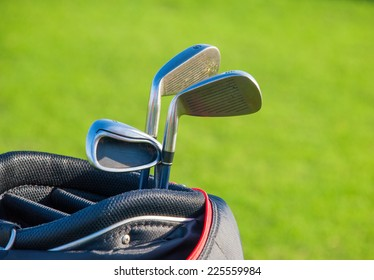 Golf club. Bag with golf clubs Green golf field and ball in grass