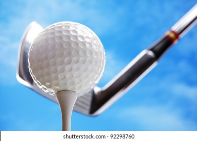Golf club and golf ball about to tee off against a blue sky