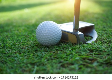 golf club and golf ball close up in grass field with sunset.Golfer long putting golf ball in to the hole, sunset scene time.