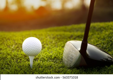 The Golf club and golf ball close up in grass field with sunset.