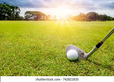 Golf club and golf ball in grass in sunrise.