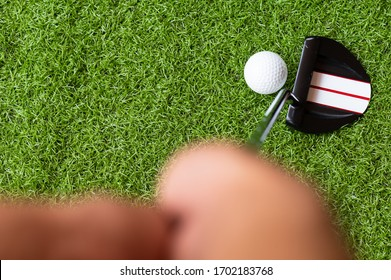Golf club and golf ball on green grass background.Golf player at the putting green hitting ball into a hole.Outdoor sport.