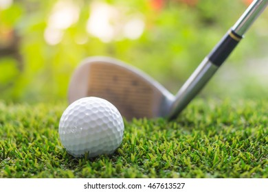 Golf club and ball on green grass