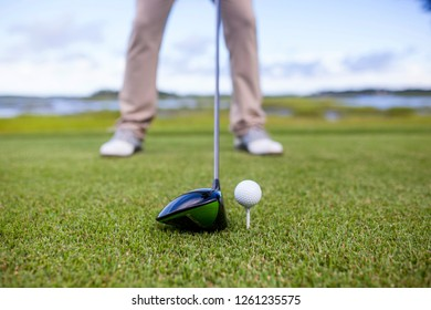 golf club and golf ball on tee, focus on the head of the club and ball.