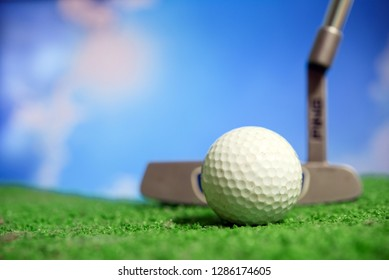 Golf club and golf ball on tee in grass.