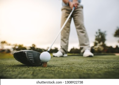 Golf club and golf ball on tee at driving range. Focus on the head of the club and ball.