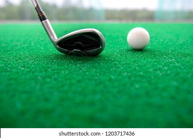 Golf club and balls on a synthetic grass mat at a practice range.