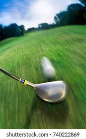 Golf club hitting ball on golf course