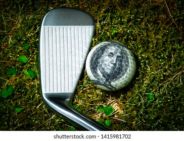 A golf club laying on the ground next to a golf ball with a 100 dollar bill on the inner cover against a grass fairway background.  The concept is that golf is an expense sport.