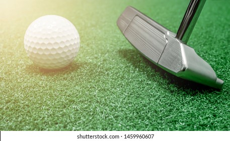 Golf club putter and golf ball placed on artificial grass with warm light and copy space included