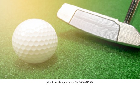 Golf club putter and golf ball placed on artificial grass with warm light