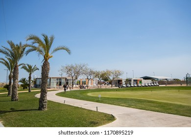 Golf clubhouse with palm trees, buggies and putting green at golf course in Spain on a summer day with clear blue sky