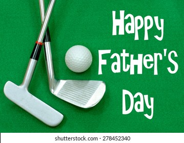 Golf clubs and golf ball on green felt background. Happy Father's Day message in white on the green felt. Clubs are a putter and a wedge, crossed, with a golf ball positioned above.  Horizontal image
