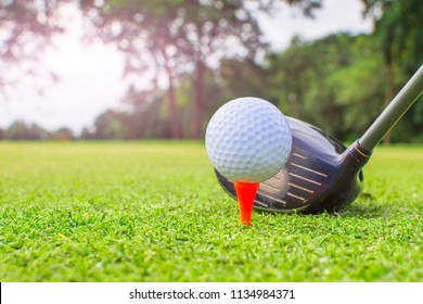 Golf clubs and golf balls on red tee.