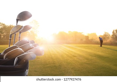 Golf clubs drivers and Golfer putting golf ball on the green  over beautiful golf course at the sunset, sunrise time. , morning time