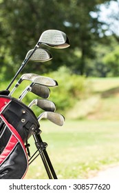 Golf clubs drivers on green field background