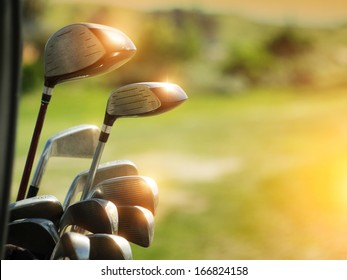 Golf clubs drivers over green field background