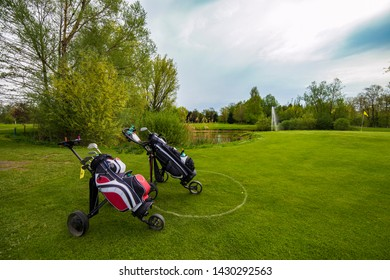 Golf clubs on the golf course with a cart